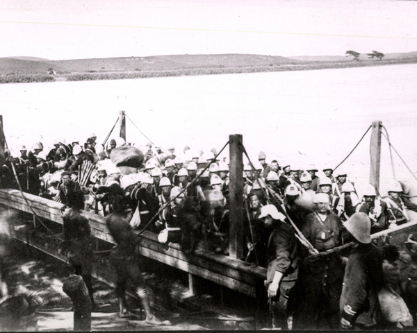 A company of the 99th Regiment crossing into Zululand by barge, 1879