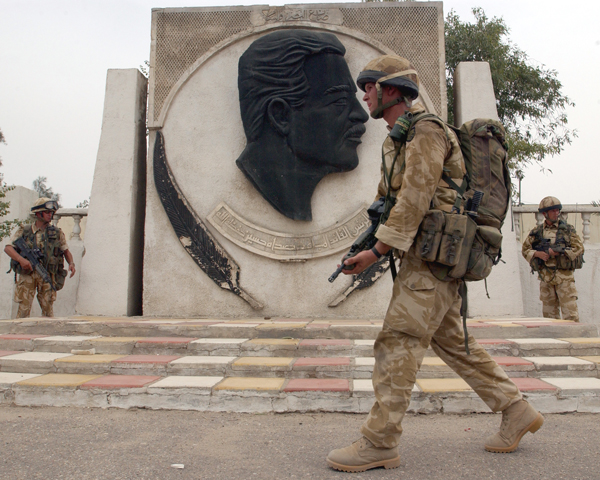A soldier of 3 Para passes a monument to Saddam, Basra, April 2003