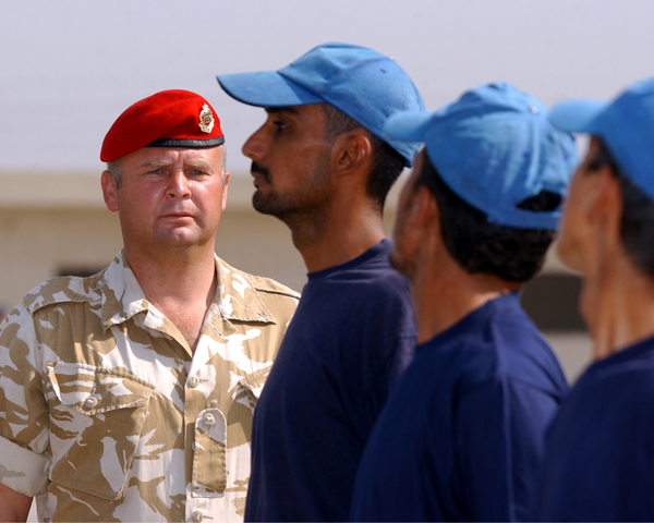 A Royal Military Policeman instructs Iraqi police recruits, 2003