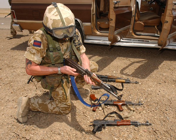 Checking arms discovered during a vehicle search, Iraq, 2003