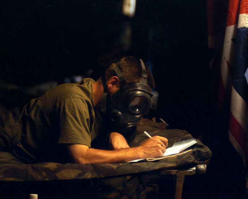 A soldier writes home during a chemical weapon alert in the Kuwaiti desert, 2003
