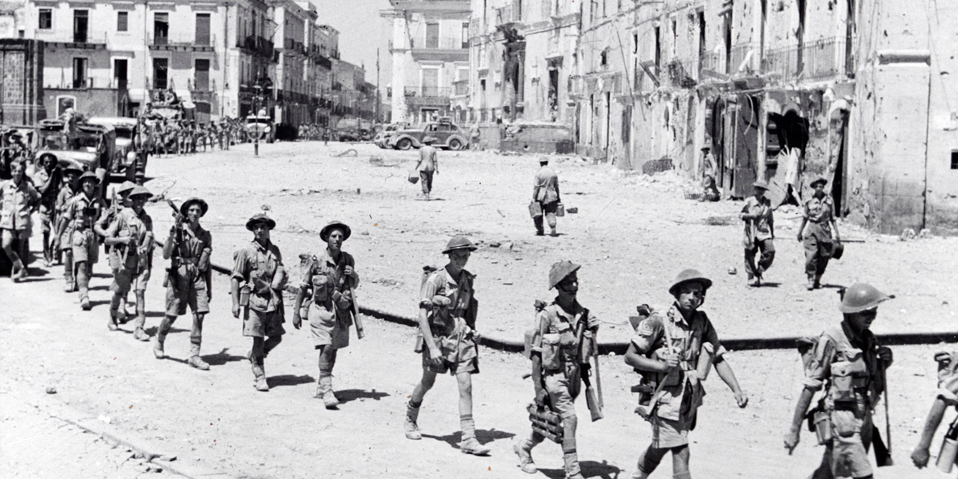 Men from the 5th Battalion, The Northamptonshire Regiment, entering the town of Adrano, Sicily, August 1943