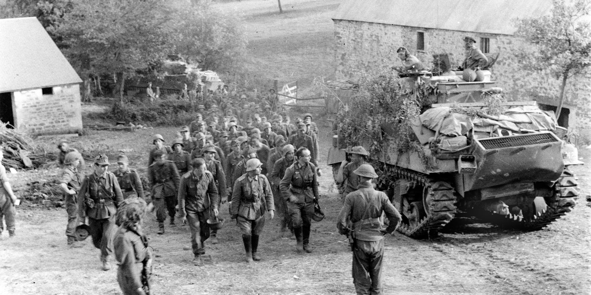 German prisoners marching past a Sherman tank, Normandy, 1944