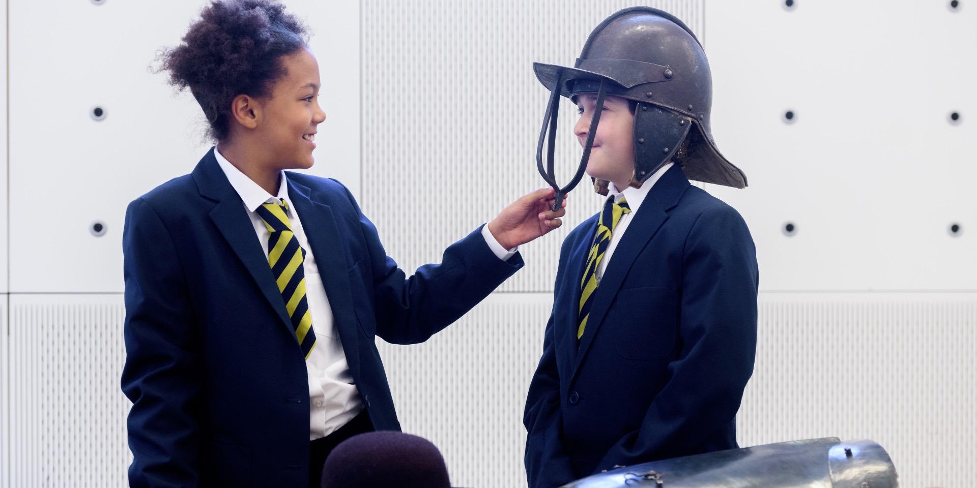 School children examining 17th-century military uniform