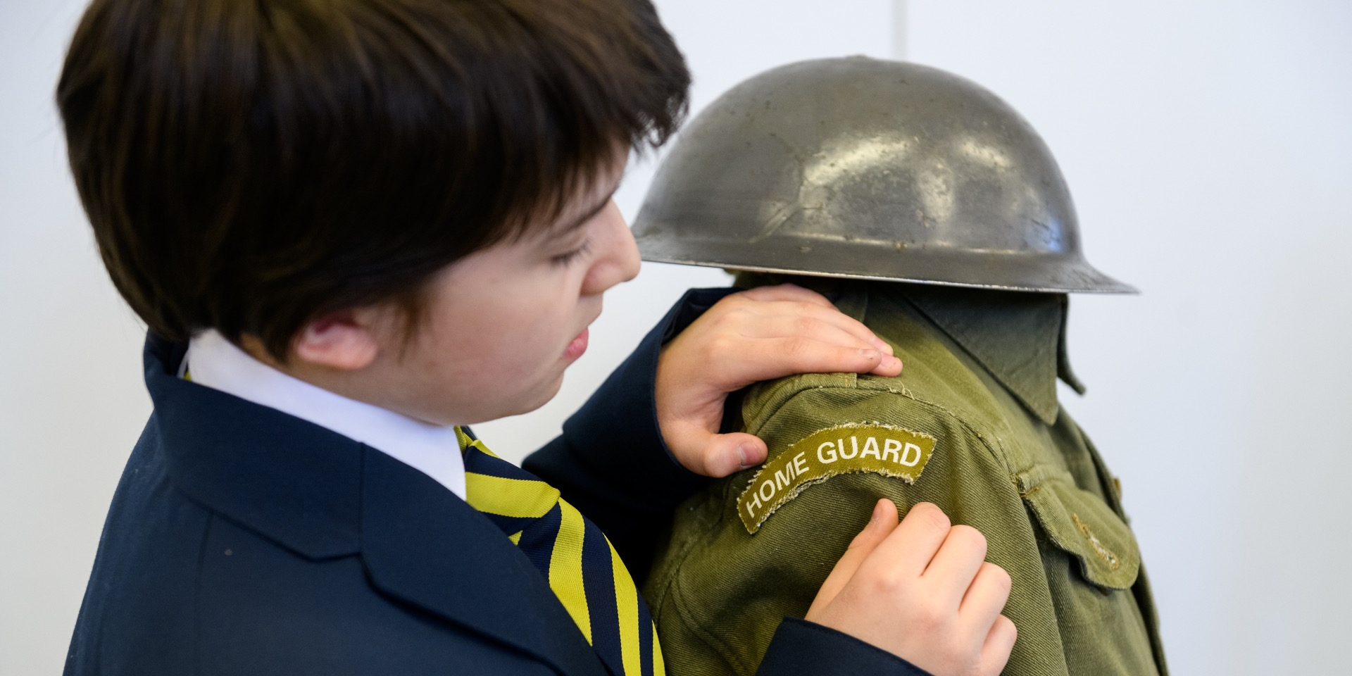 School boy examining a Home Guard uniform