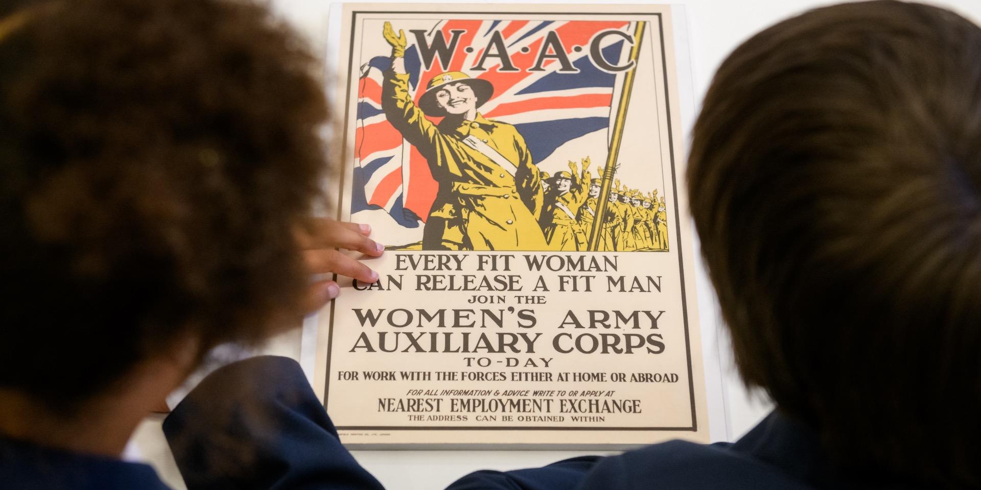 School children examining a First World War recruiting poster