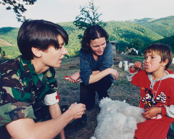 An Army dentist and interpreter with a local child, 1999