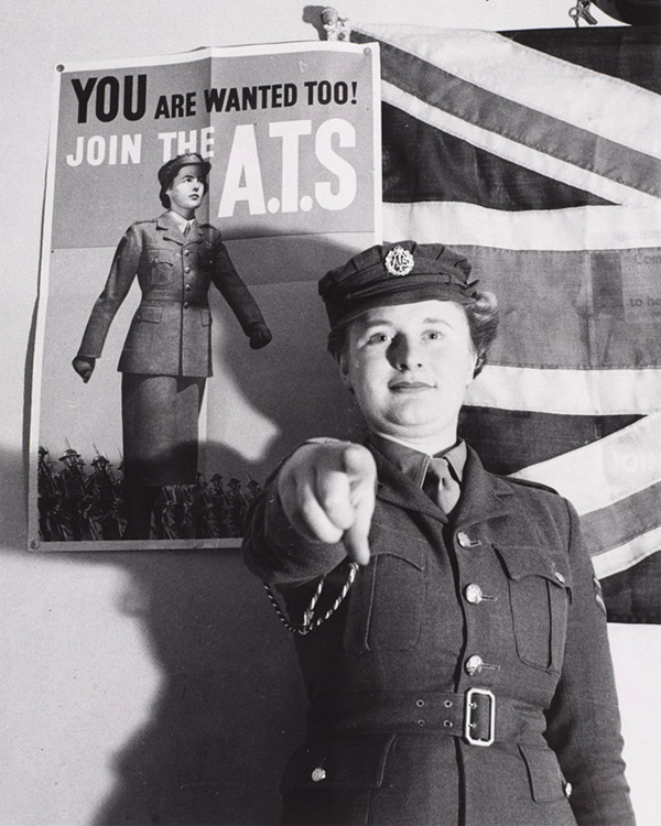 Private Mary Catherine Roberts posing alongside her recruiting poster, c1941