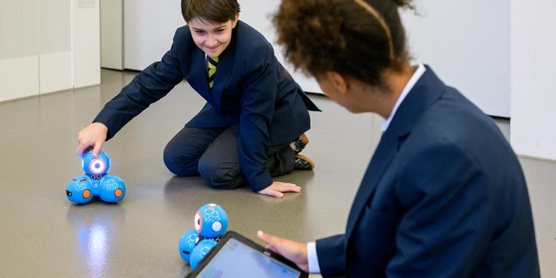 School children working with Dash robots