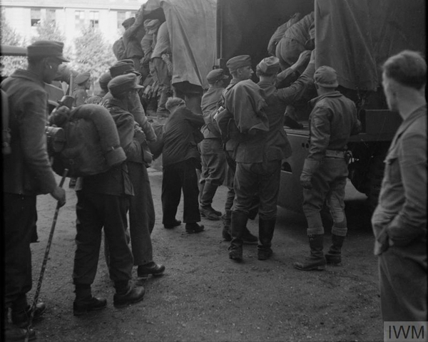Demobbed German soldiers boarding lorries at Eutin barracks to be taken to various location to undertake reconstruction work, June 1945