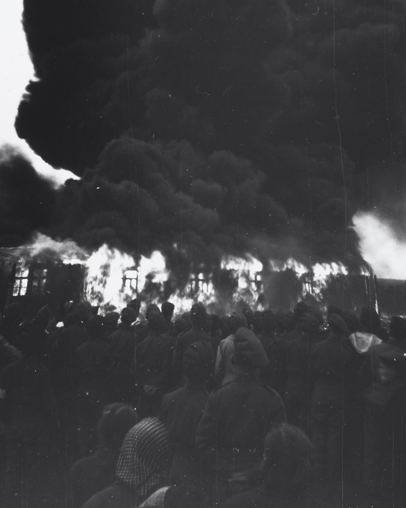 Soldiers and civilians watch the burning of Belsen, 21 May 1945