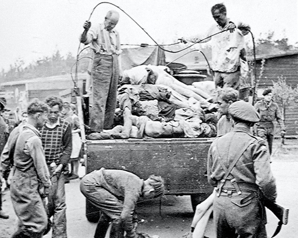 A British soldier guards SS members as they collect the dead at Belsen Concentration Camp following its liberation, April 1945