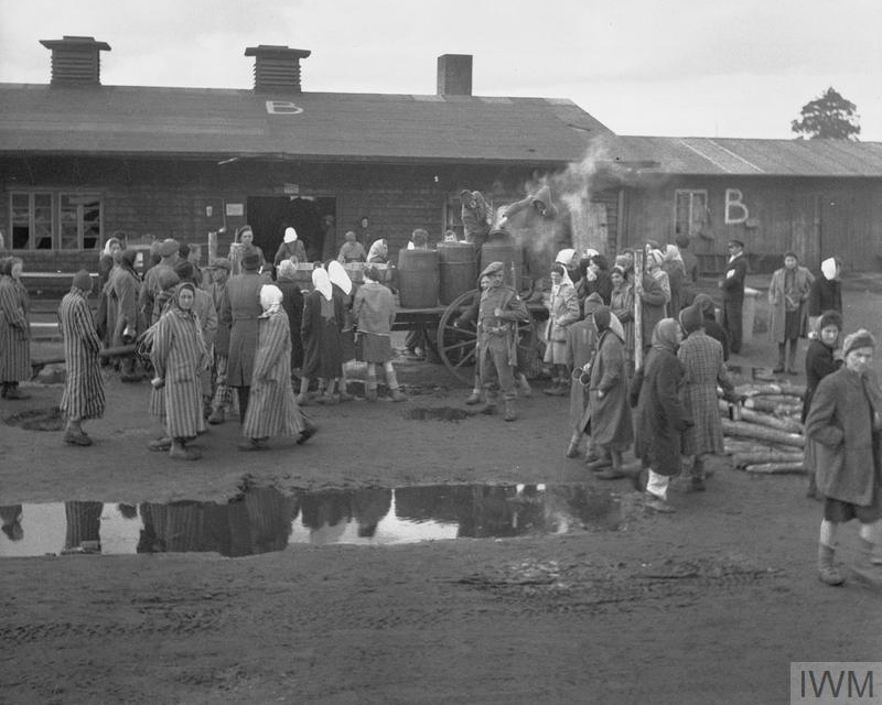 British soldiers supervise the distribution of food to camp inmates, April 1945