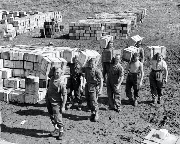 A 'compo ration' dump and men carrying supplies to it, March 1943