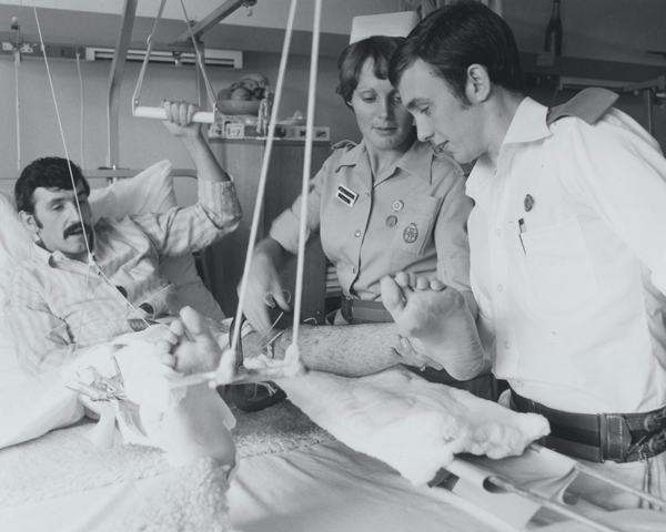 A QARANC nurse helps removes the plaster cast from a patient's leg, 1975