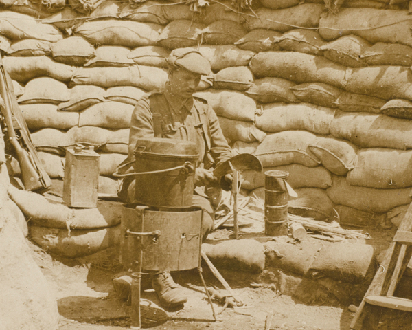 A cook preparing food in a dixie on a charcoal fire at the front, 1915