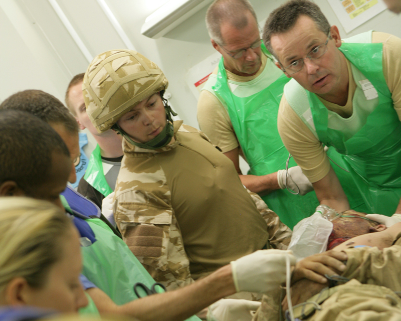 A MERT medic (in combat fatigues) oversees the handover of a casualty to the staff at Camp Bastion, 2007