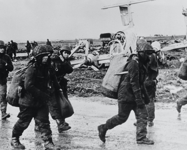 Argentine prisoners pass a wrecked Pucara aircraft, Goose Green, 1982