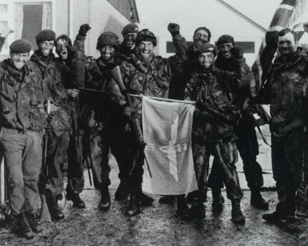 Men of the 3rd Parachute Regiment with their regimental ensign after the liberation of Port Stanley, June 1982