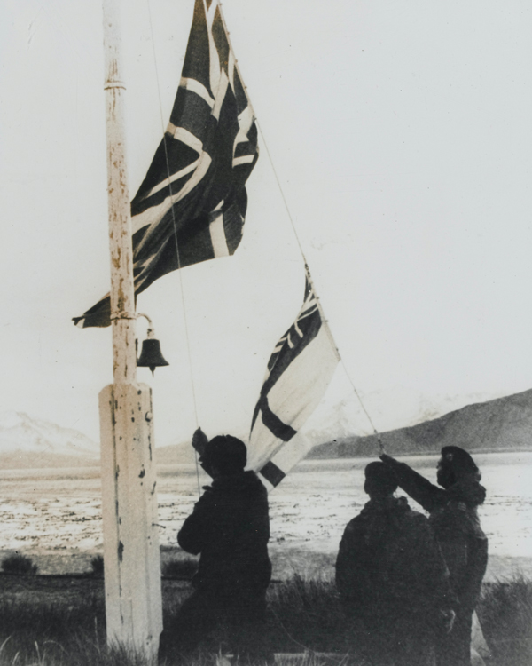 Royal Marines hoisting the Union Jack and White Ensign over Grytviken, capital of South Georgia, April 1982