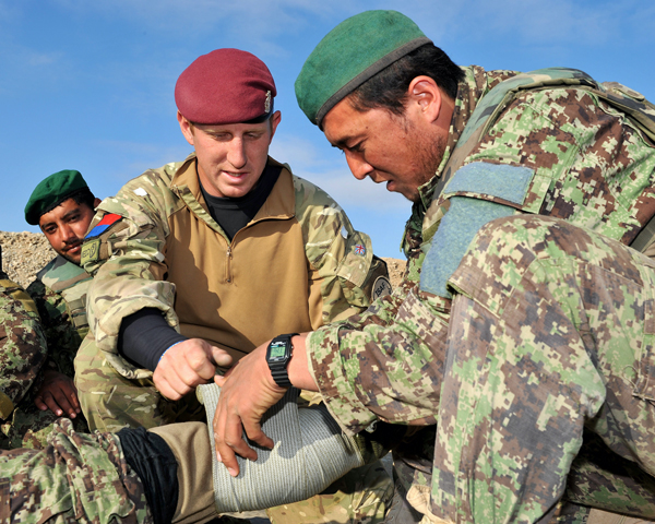 Corporal Harvey Davies, Royal Army Medical Corps, training an Afghan soldier to apply a field dressing, 2011