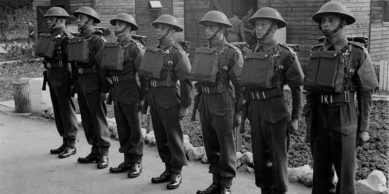A parade of soldiers in helmets, gas mask cases on their chests and holstered revolvers at their sides