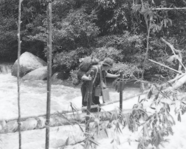 A members of the Coldstream Guards crossing a river in Malaya, c1948