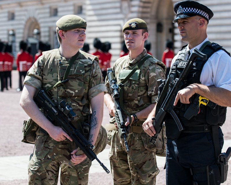 Coldstream Guardsmen with an armed police officer at Buckingham Palace during Operation Temperer, 2017