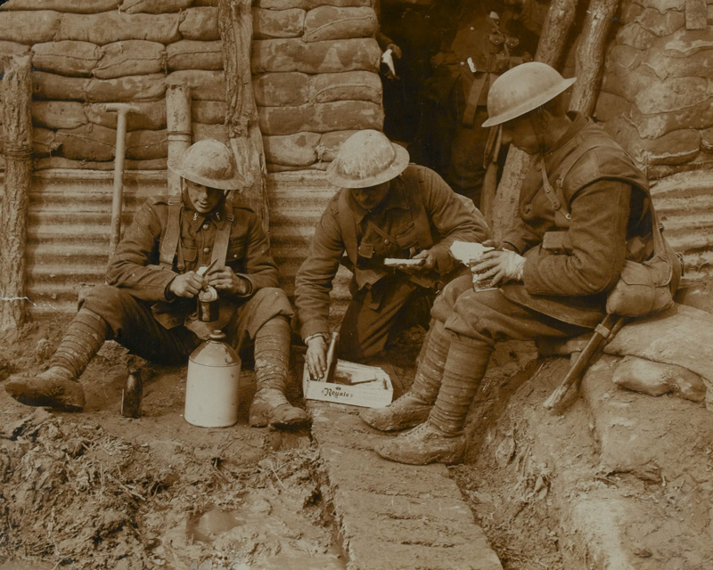 Soldiers with their rum ration in a trench, c1917