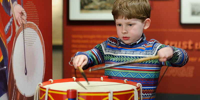Child playing on a drum