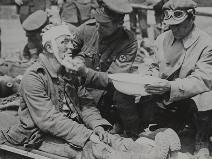 A British medical orderly treats a wounded German soldier, c1916
