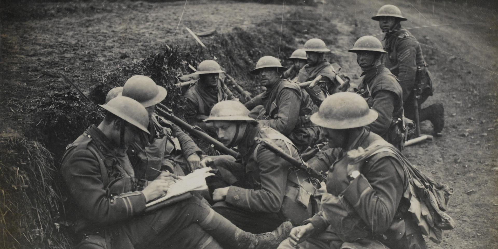 Soldiers rest in a ditch as their officers consult a map, 16 April 1918