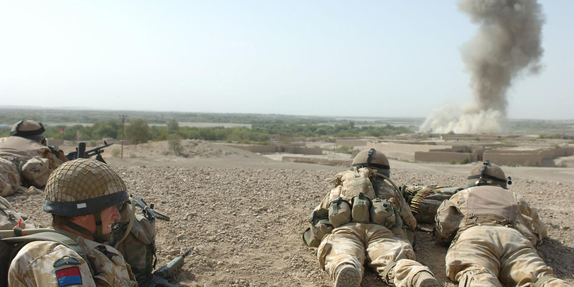 British soldiers watching the after effects of a 500lb bomb dropped on an enemy position in Musa Qala