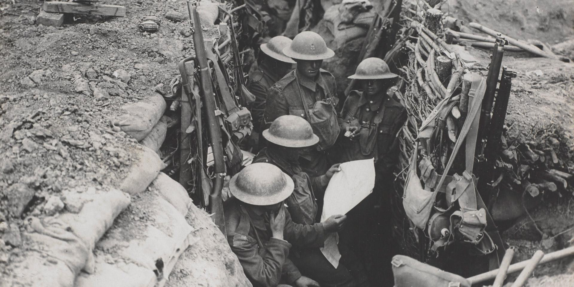Soldiers reading a newspaper in the trenches, c1916