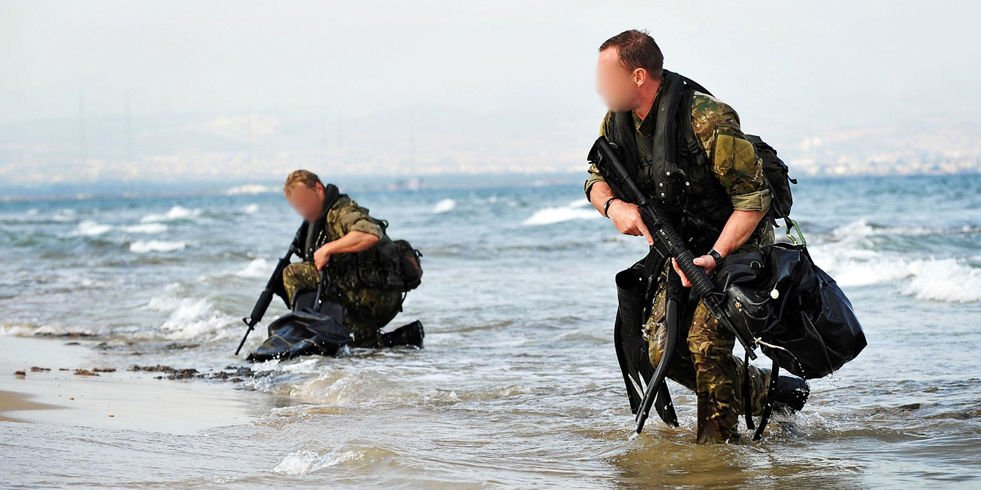Two SBS Swimmer canoeists emerge from the sea with weapons ready, c2010