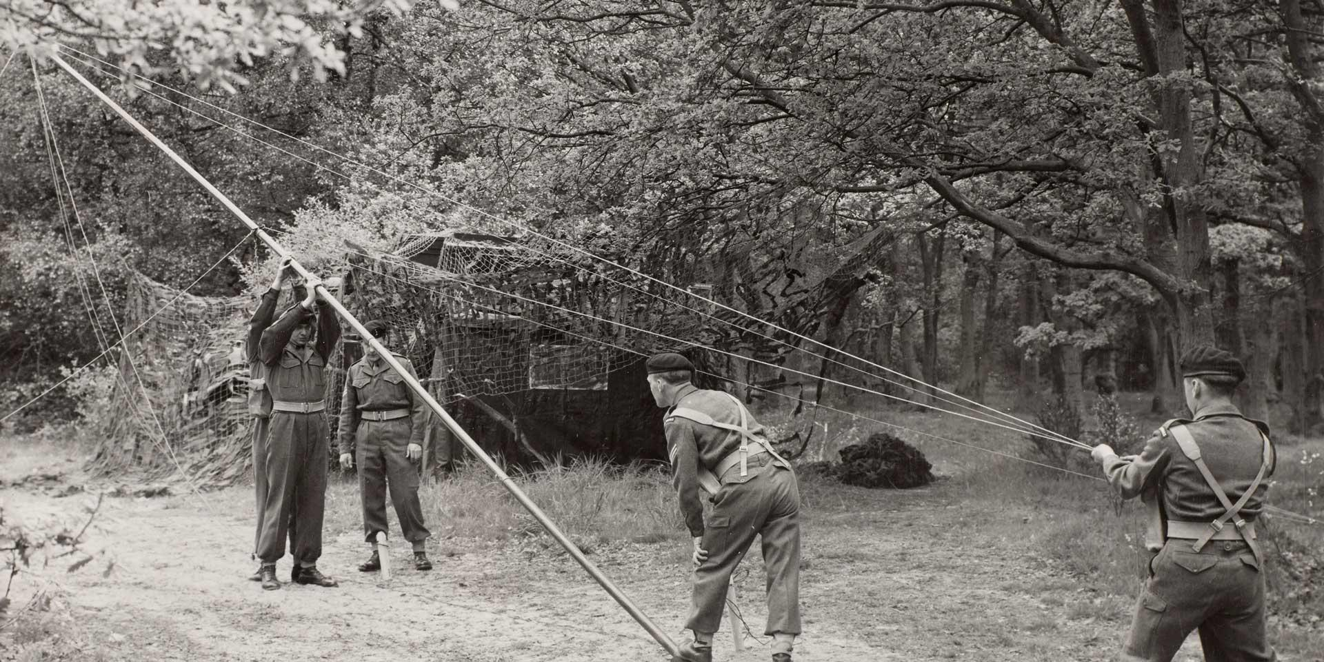 Royal Corps of Signals soldiers erect a radio aerial, c1955