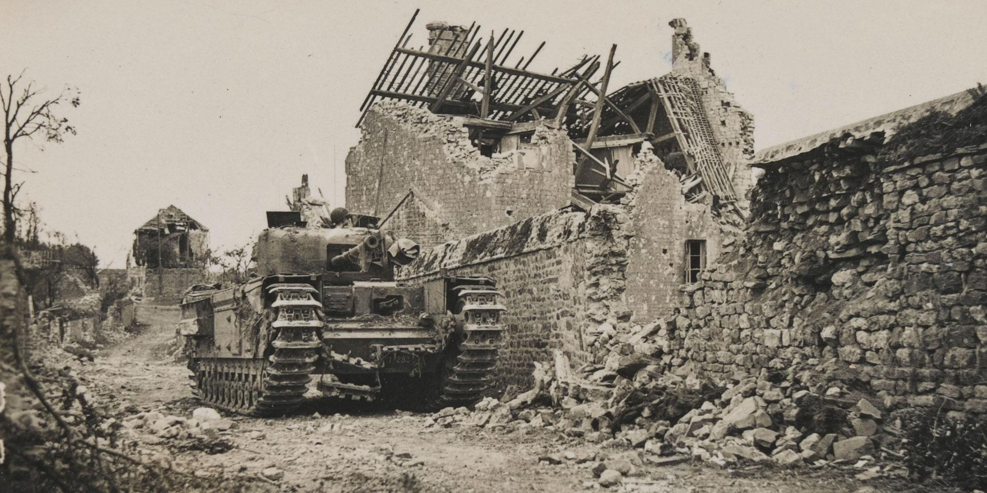 A Churchill tank awaits possible enemy counter-attack in a ruined village, 1944