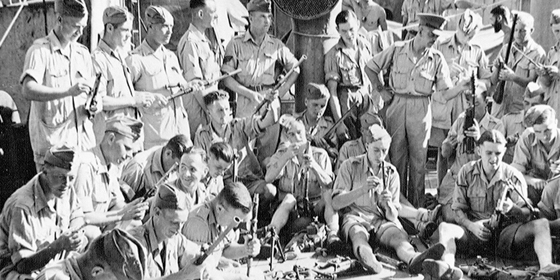 1st Battalion The Durham Light Infantry cleaning weapons on board the 'Winchester Castle', July 1943