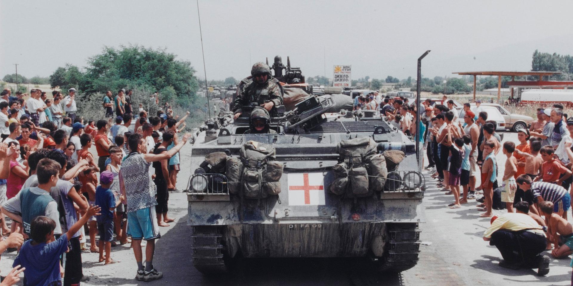 A British Warrior tracked vehicle passing Stenkovich refugee camp on the Macedonia-Kosovo border, 1999