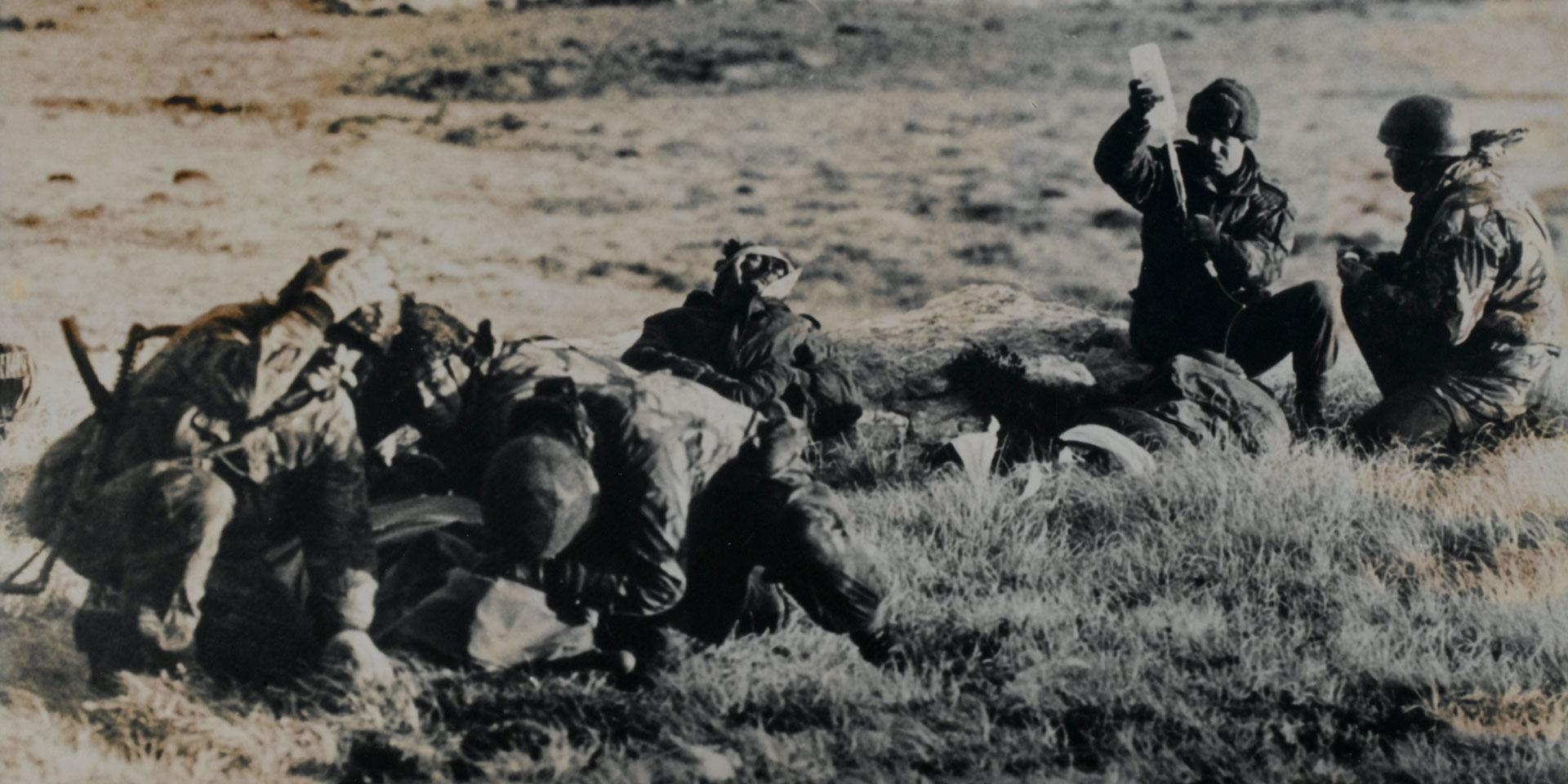 Paramedics attending a wounded Argentine soldier under fire, Mount Longdon, Falkland Islands, 1982