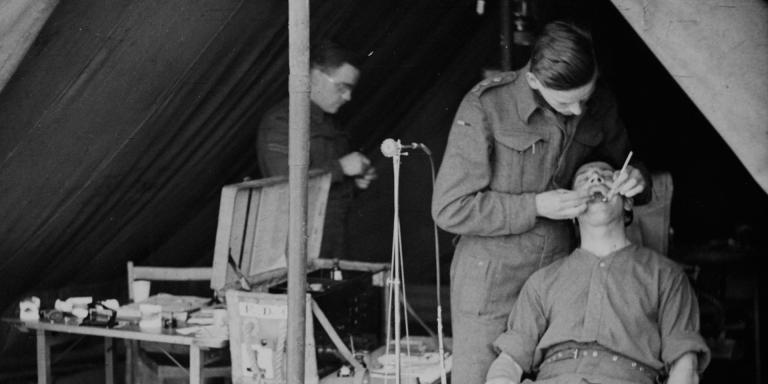 Captain Rushby practising dentistry on a patient in the front line, Tunisia, February 1943