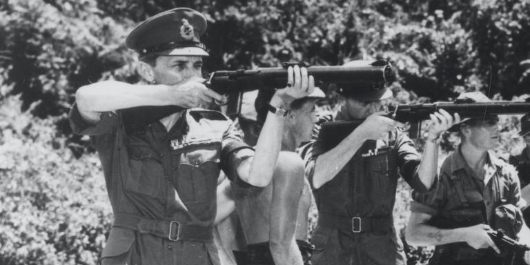 General Sir Gerald Templer (left) testing a De Lisle machine-gun during a visit to 1st Battalion The Gordon Highlanders, south Perak, 1952