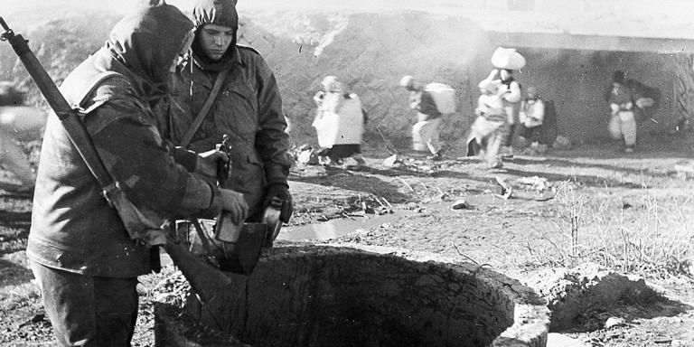 Members of The Middlesex Regiment, wrapped against the bitter Korean winter, draw water from a well, 1951