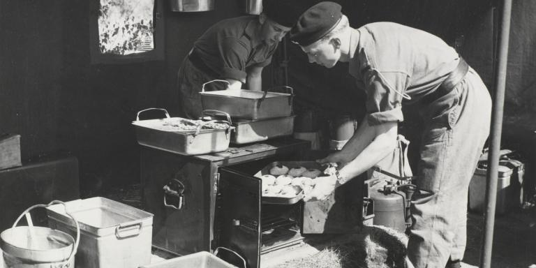 Army Catering Corps soldiers prepare a meal in a field kitchen, c1958