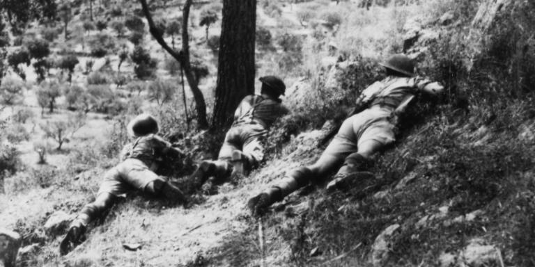 Soldiers of the 6th Royal Inniskilling Fusiliers take cover in an olive grove, Italy, November 1943