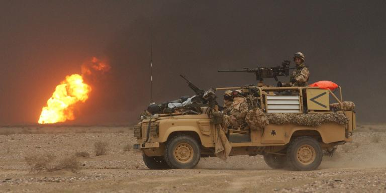 A Royal Irish Regiment vehicle passes a burning oil well during the invasion of Iraq, March 2003
