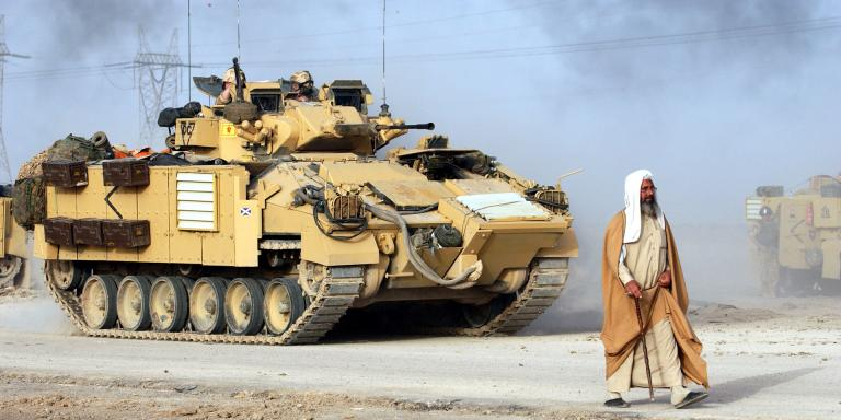 A civilian walks in front of a Warrior Infantry Fighting Vehicle, Iraq, March 2003